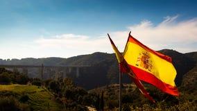 Spansk flagga med blå himmel och bron royaltyfria bilder