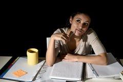 Spansk flicka som studerar tröttat och borrat hemma sent - frånvarande sinnat se för natt fundersamt och lyckligt Arkivfoto