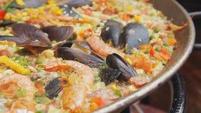 Spansk paella med gula ris, räkor och musslor som lagar mat på maten, marknadsför Gatamatfestival Rice med skaldjur stock video