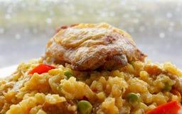 Spansk paella och guld- Fried Chicken lår mot regnig fönsterbakgrund Royaltyfri Bild