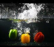 spansk peppar En grupp av söta peppar som ner faller, och splashin arkivfoton