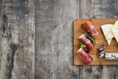 Spansk serranoskinka, ost och korv på en lantlig träbakgrund Fotografering för Bildbyråer
