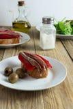 Spansk tapa - skiva av bröd med den grillad röd peppar, ansjovisen och olivolja royaltyfri bild