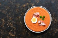 Spansk tomatsoppa Salmorejo tjänade som i en grå platta med skinka och ägget Bästa sikt, kopieringsutrymme arkivfoto