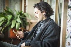 Spansk ung man som använder smartphonesammanträde på en terrass arkivbild