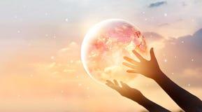 Spara aktionen för världsenergi Planetjord på mänsklig handshow royaltyfri bild