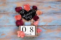 Spara datumkvarterkalendern för internationella kvinnors dag, mars 8, med den svart tavlan, bredvid rosblommor, på blått royaltyfri foto