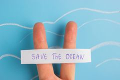Spara havbegreppet två fingrar med att sjunga sparar havet arkivbilder