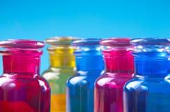 Spara kulöra små flaskor och deras glass stordia Arkivbild