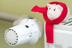 Spara pengaruppvärmningbegreppet med termostaten och spargrisen arkivbilder