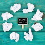 Spara planetbegreppet - skrynkligt papper runt om en svart tavla i form av hjärta och text Please återanvänder royaltyfri foto