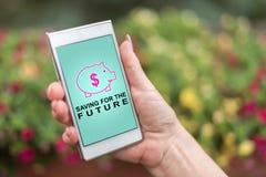 Sparande inför framtiden av begrepp på en smartphone royaltyfria bilder