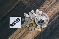 Sparande mynt i krus arkivbilder