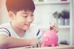 Sparande pengar för asiatisk pys i den rosa spargrisen royaltyfri bild