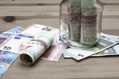 Sparande pengar för hus- och bilbegrepp Arkivbild