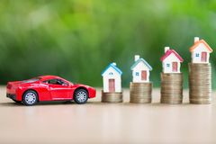Sparande pengar för huset och bilen, som staplar det guld- myntet som växer, sav arkivbilder