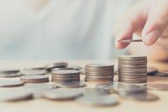 Sparande pengar för investeringbegrepp, handen av manligt eller kvinnlign sätter arkivbild