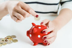 Sparande pengar för kvinna med den röda spargrisen Royaltyfri Fotografi