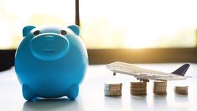 Sparande pengar för loppbegrepp Blå peggy bank med flygplanet och mynt royaltyfria foton