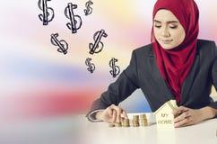 Sparande pengar för lyckad ung muslimah för hennes dröm- hus över abstrakt bakgrund för dubbel exponering Arkivfoto