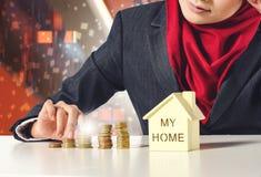 Sparande pengar för lyckad ung muslimah för hennes dröm- hus över abstrakt bakgrund för dubbel exponering Royaltyfria Bilder