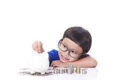 Sparande pengar för pojke arkivbilder