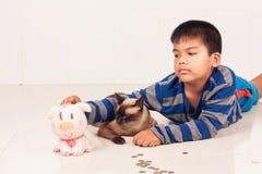 Sparande pengar för asiatisk pojke i piggybank Arkivfoton