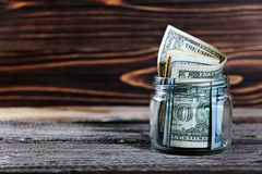 Sparande pengar i kruset med amerikanska dollar, kassa royaltyfria foton