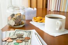 Sparande pengar- och kaffeavbrott Arkivbild