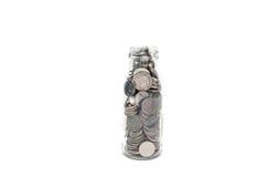 Sparande pengarbegrepp av att samla mynt i glasflaskaisolat Arkivfoto