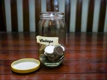 Sparande pengarbegrepp med högskolatext som är skriftlig på den Glass kruset Selektivt fokusera och bli grund DOF Arkivfoto