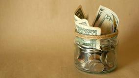 Sparande pengarmynt i krus Symbol av att investera som håller pengarbegrepp Samla kontanta sedlar i glass tenn som moneybox lager videofilmer