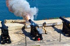 Sparato da una pistola a mezzogiorno in batteria di saluto a Lascaris forte, La Valletta, Malta fotografie stock libere da diritti