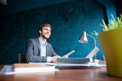 Sparato del giovane che si siede alla tavola che distoglie lo sguardo e che pensa Uomo d'affari premuroso che si siede nell'uffic immagini stock libere da diritti