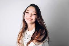 Sparato della giovane donna alla moda che sorride contro il fondo bianco Bello modello femminile con lo spazio della copia Felici fotografia stock