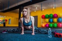 Sparato della giovane donna che allunga alla palestra Femmina muscolare che fa gli esercizi per allungare il suo corpo sul pavime Immagini Stock Libere da Diritti
