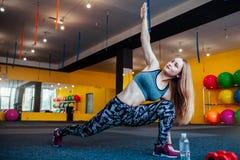Sparato della giovane donna che allunga alla palestra Femmina muscolare che fa gli esercizi per allungare il suo corpo sul pavime Fotografie Stock Libere da Diritti
