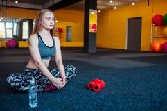 Sparato della giovane donna che allunga alla palestra Femmina muscolare che fa gli esercizi per allungare il suo corpo sul pavime Immagini Stock
