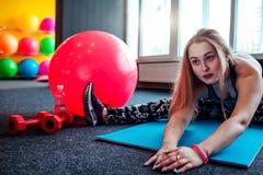 Sparato della giovane donna che allunga alla palestra Femmina muscolare che fa gli esercizi per allungare il suo corpo sul pavime Fotografia Stock Libera da Diritti