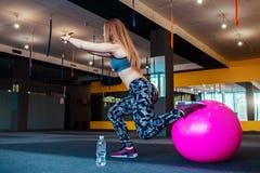 Sparato della giovane donna che si esercita alla palestra Addestramento femminile muscolare facendo uso di una palla Donna che fa Fotografie Stock