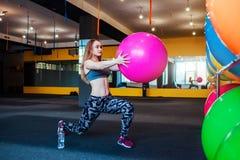 Sparato della giovane donna che si esercita alla palestra Addestramento femminile muscolare facendo uso di una palla Donna che fa Immagine Stock