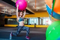 Sparato della giovane donna che si esercita alla palestra Addestramento femminile muscolare facendo uso di una palla Donna che fa Immagini Stock Libere da Diritti