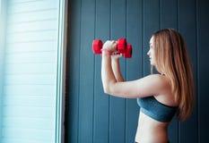 Sparato della giovane donna che si esercita con le teste di legno alla palestra Addestramento femminile muscolare davanti alla fi Immagini Stock