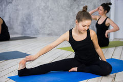 Sparato delle giovani donne che si scaldano prima della sessione di yoga I giovani che si siedono sulla stuoia di esercizio nell' Fotografie Stock Libere da Diritti