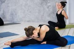 Sparato delle giovani donne che si scaldano prima della sessione di yoga I giovani che si siedono sulla stuoia di esercizio nell' Immagini Stock