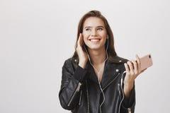 Sparato di bella ragazza caucasica urbana con capelli biondi che tengono smartphone rosa d'avanguardia, musica d'ascolto in cuffi Fotografia Stock Libera da Diritti