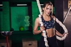 Sparato di un atleta femminile attraente del crossfit con una corda alla palestra fotografia stock