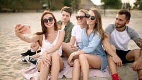 Sparato di un gruppo di giovani amici che prendono un selfie sulla spiaggia Uomini e donne che prendono le foto che si siedono su video d archivio