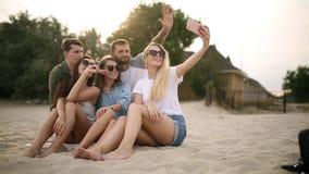 Sparato di un gruppo di giovani amici che prendono un selfie sulla spiaggia Uomini e donne che prendono le foto che si siedono su stock footage