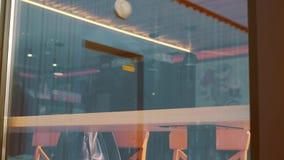Sparato di un uomo che si siede in caffè con uno smartphone Sparato attraverso la finestra di manifestazione del caffè archivi video